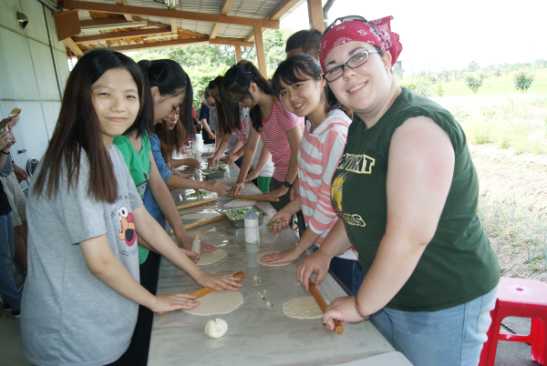 Kate Steinel (far right) joins the Cardinal Tien students in making organic onion cakes.